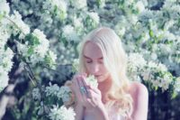 Blond-haired woman smelling white tree flowers photo by Sharon McCutcheon